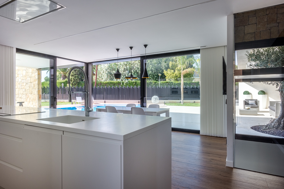 Cocina moderna con isla en casa de diseño Cumbres con vistas al jardín