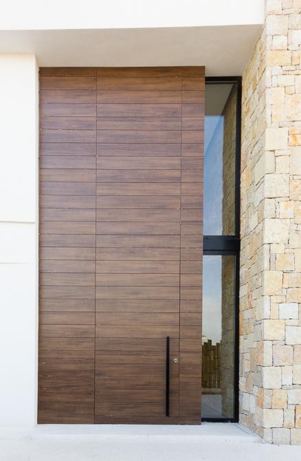 Puerta de entrada principal en madera y piedra en casa de diseño Cumbres | Chiralt Arquitectos Valencia