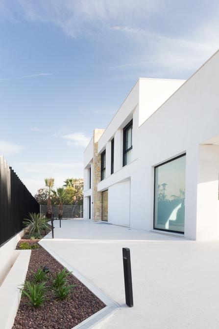 Entrada principal con suelo de hormigón blanco y muro de piedra Cumbres | Chiralt Arquitectos Valencia