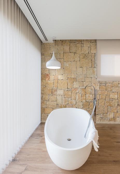 Dormitorio con bañera integrada y vistas al jardín en tonos claros en casa de diseño Cumbres   Chiralt Arquitectos Valencia