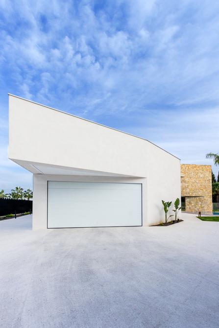 Garaje moderno con voladizo en blanco en casa de diseño Cumbres | Chiralt Arquitectos Valencia