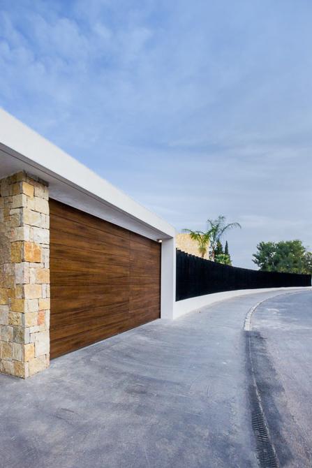 Puerta de garaje en madera y piedra en casa de diseño Cumbres   Chiralt Arquitectos Valencia