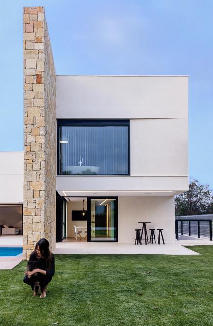 Fachada minimalista con muro de piedra en casa de diseño Cumbres