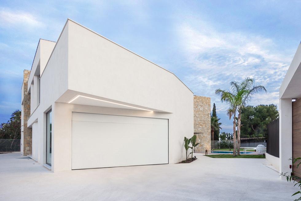 Garaje moderno con voladizo en blanco en vivienda de diseño Cumbres Chiralt Arquitectos Valencia