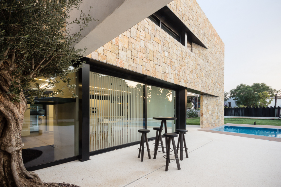 Muro de piedra en casa de diseño Cumbres con terraza y piscina   Chiralt Arquitectos Valencia
