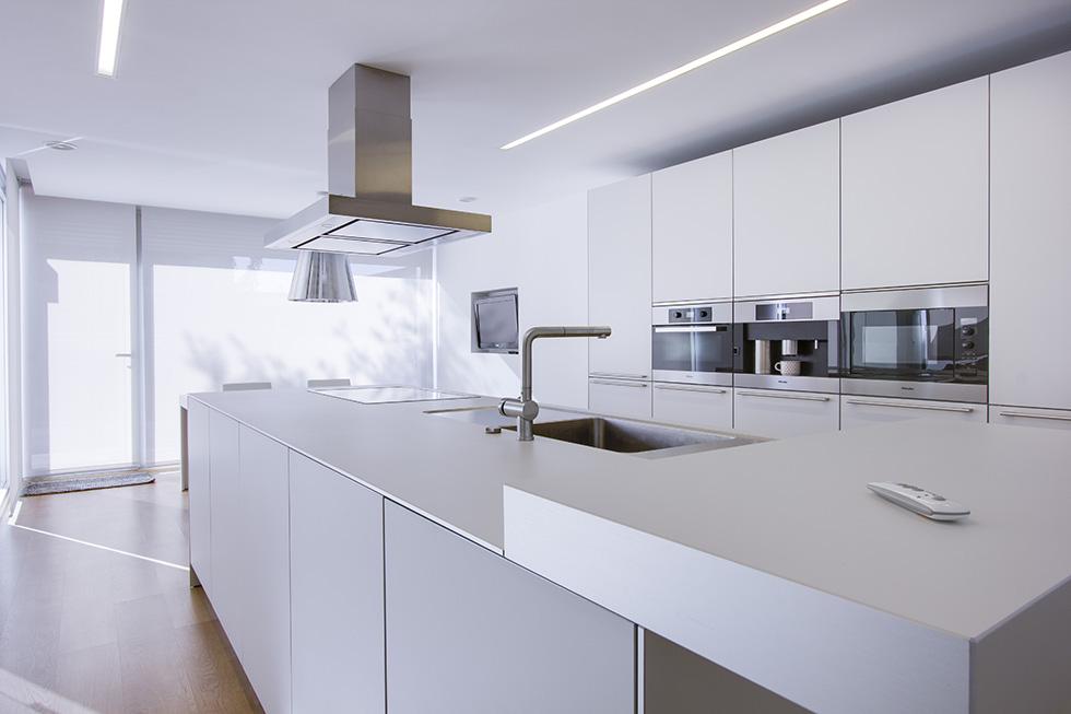 Impresionante cocina blanca, con isla central con encimera y fregadero. Abierta al jardín con grandes ventanales.