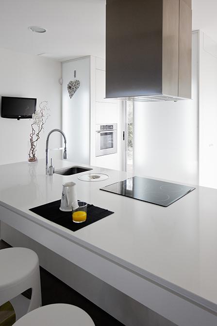Cocina blanca con isla en casa minimalista. Chiralt Arquitectos Valencia.