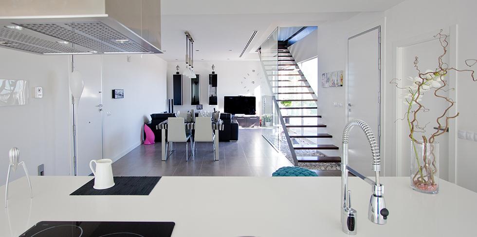 Escalera con barandilla de cristal en cocina salón de casa minimalista