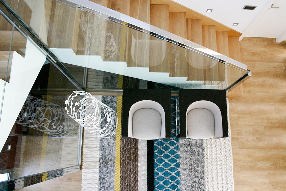 Recibidor moderno con escalera de madera y cristal, con sillones Stua y alfombra Gan. Antes y después de una reforma integral | Chiralt arquitectos Valencia | Casa La Pobla