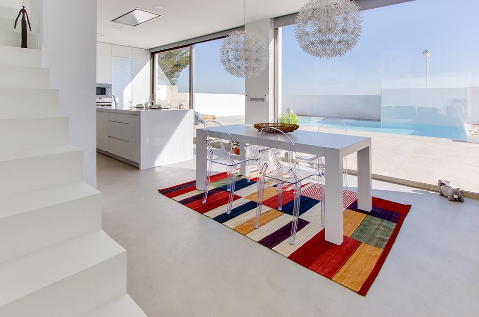 Isla de cocina en blanco integrada en el salón comedor con vistas a la piscina de microcemento blanco |Chiral arquitectos Valencia