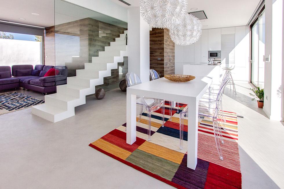 Cocina y escalera de microcemento blanco integrada en salón comedor en casa mediterranea |Chiralt arquitectos Vaencia
