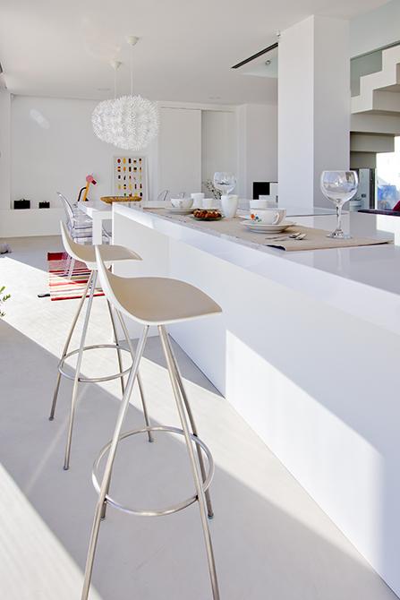 Isla de cocina central en microcemento con taburetes de Stua | Chiralt arquitectos valencia
