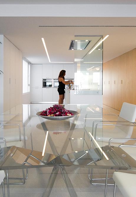 Mesa de comedor moderna de cristal en cocina integrada en el salón