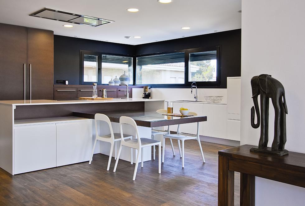 Cocina moderna en blanco y negro con suelo porcelánico efecto madera en casa pasiva