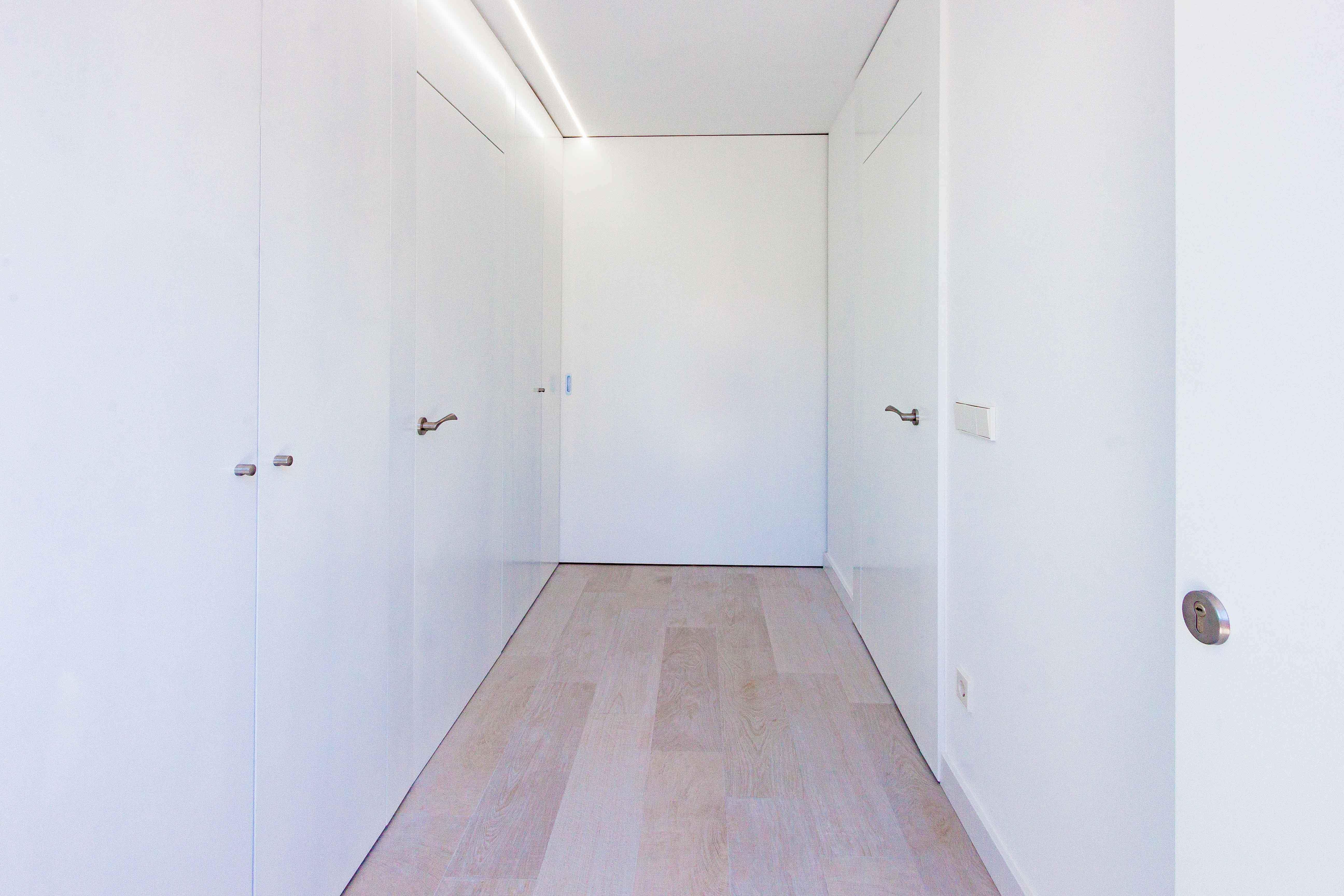 Armario empotrado con puertas enrasadas en hall de reforma de casa. Chiralt Arquitectos Valencia.