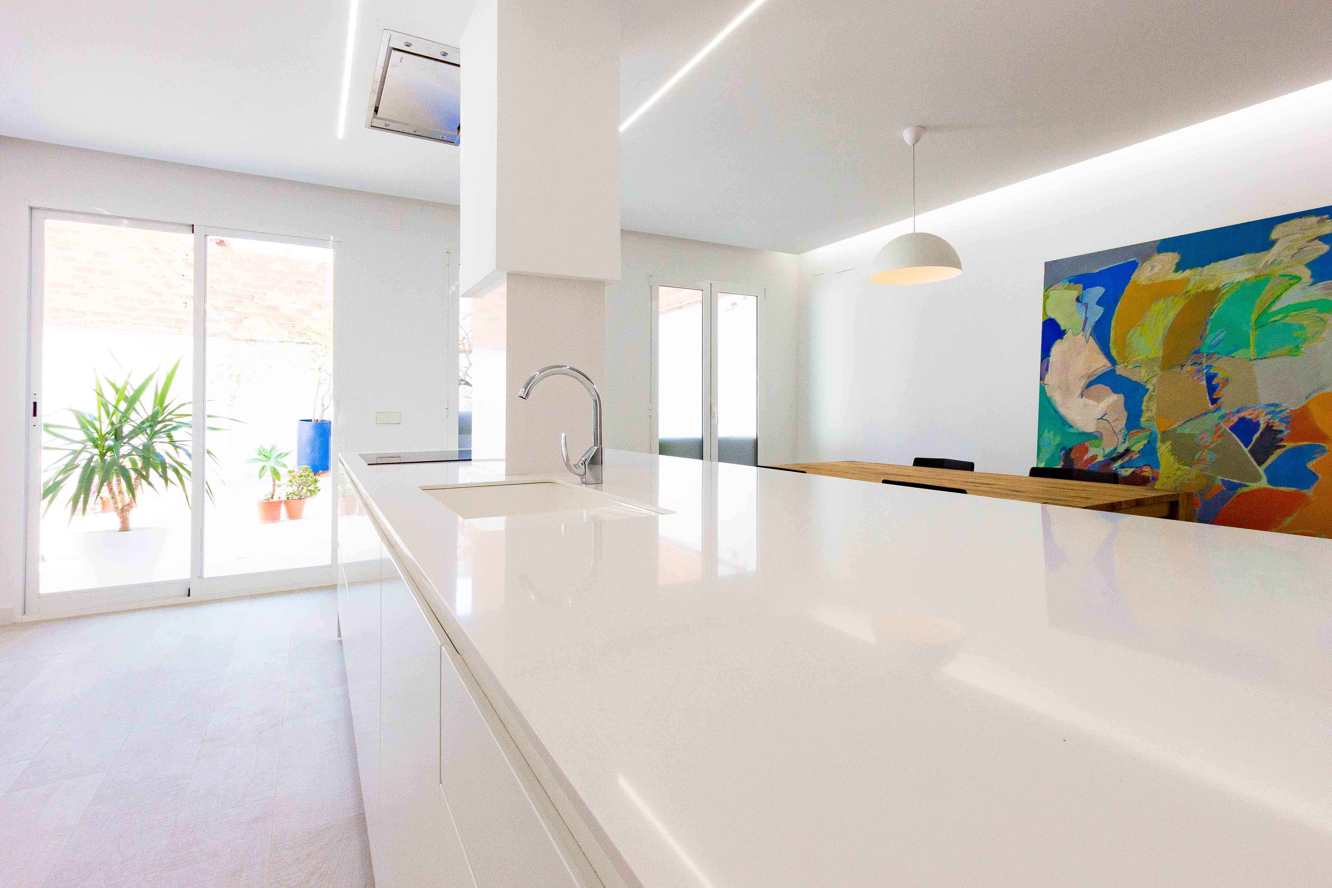 Isla en cocina blanca minimalista en reforma de casa. Chiralt Arquitectos Valencia.