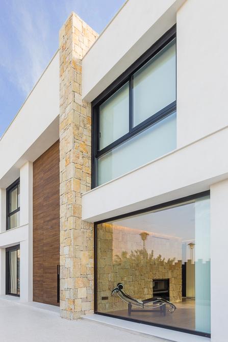 casa de diseño Cumbres con fachada de piedra y gran ventanal de Chiralt Arquitectos Valencia