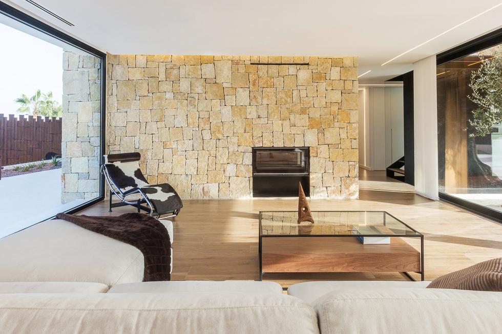 Salón con muro de piedra en casa de diseño Cumbres de Chiralt Arquitectos Valencia