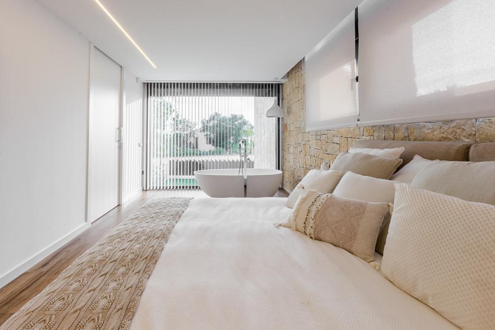 Dormitorio con bañera integrada y vistas al jardín en tonos claros en casa de diseño Cumbres de Chiralt Arquitectos Valencia