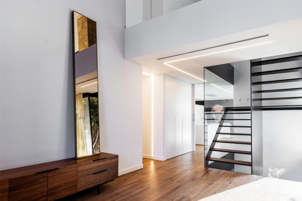 Recibidor con doble altura de piedra en casa diseño Cumbres de Chiralt Arquitectos Valencia