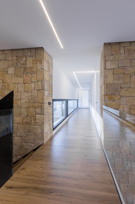 Pasillo con muro de piedra en casa de diseño Cumbres de Chiralt Arquitectos Valencia