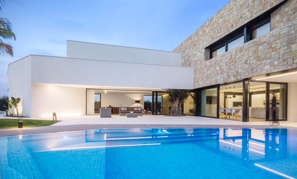 Piscina de lujo con muro de piedra en casa de diseño Cumbres de Chiralt Arquitectos Valencia