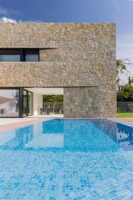 Piscina y fachada de piedra en casa de diseño Cumbres de Chiralt Arquitectos Valencia