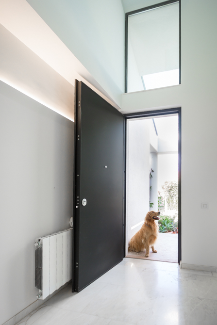 Puerta negra y suelo de mármol en vivienda mediterranea. Chiralt Arquitectos Valencia