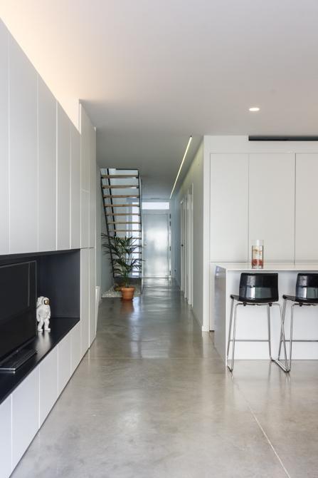 Salón con suelo hormigón armariada moderna blanca en vivienda estilo nórdico - Chiralt Arquitectos Valencia