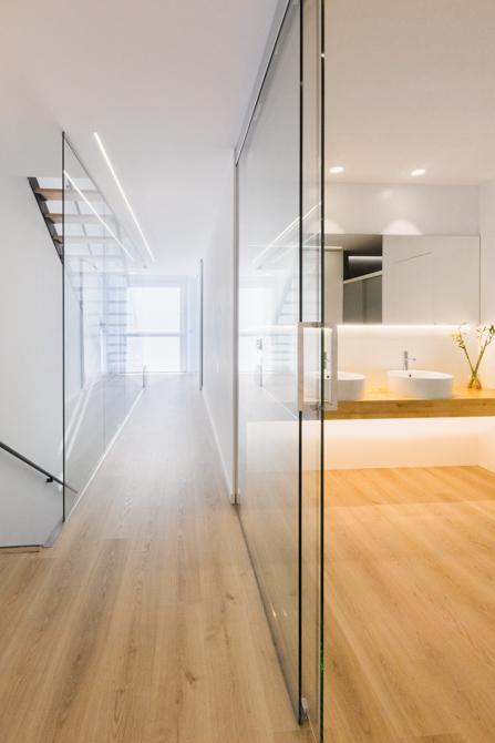 Baño moderno con puerta de cristal y pasillo moderno con suelo parquet en vivienda estilo nórdico - Chiralt Arquitectos Valencia