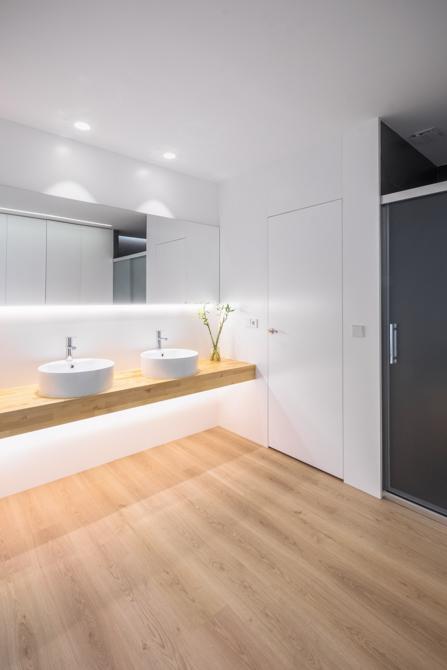 Baño moderno con dos lavabos y suelo parquet en vivienda estilo nórdico - Chiralt Arquitectos Valencia